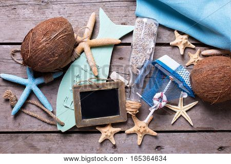 Coconuts and marine items on vintage wooden background. Empty frame for your text. Vacation background.