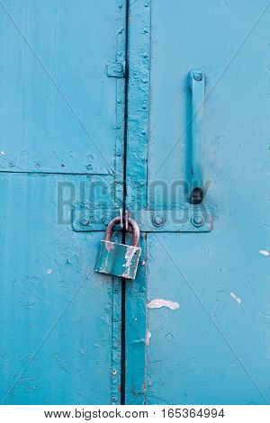 Hanging metal lock on turqoise paint color metallic door. Closed private object vintage style