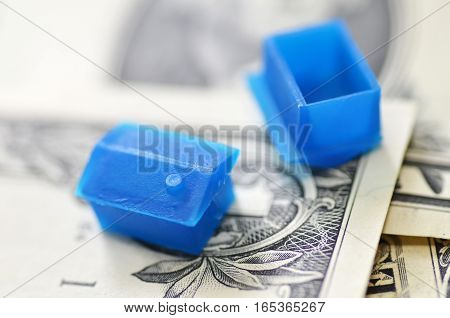 Little plastic house on US dollar banknote real estate and property concept