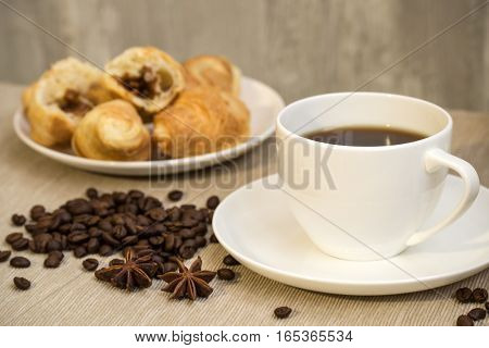 White cup of coffee and croissants with coffee beans scattered on the table