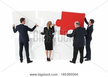Business team builds a new project with puzzle isolated on white