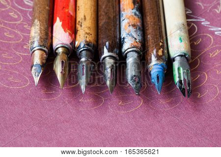 Fountain pen collection. Calligraphic accessories, aged colorful artist pens, textured paper background. Artist workshop concept. macro, up view, soft focus