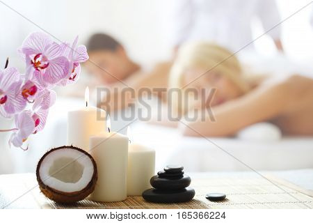 Spa massage tools and women getting massage on background