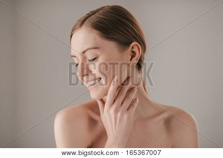 Sensitive care for a luminous skin. Portrait of redhead woman with freckles keeping eyes closed and smiling while touching her face and standing against grey background
