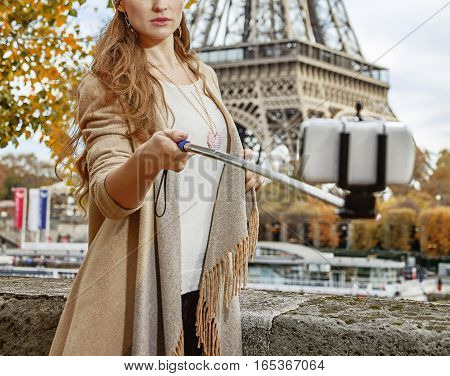 Autumn getaways in Paris. young elegant woman on embankment near Eiffel tower in Paris France taking selfie using selfie stick