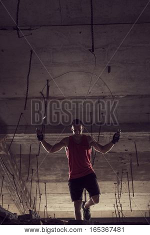 Young athlete jumping rope at an abandoned building working out