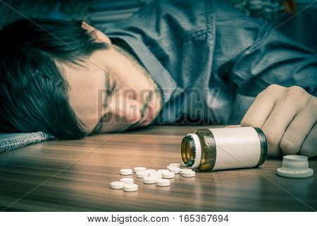Suicide Attempt. Young Man Is Lying On Table. A Lot Of Pills Aro