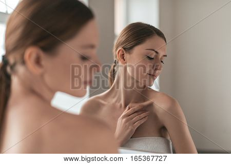 Natural beauty. Over the shoulder view of young woman touching her skin and looking away while standing in front of the mirror