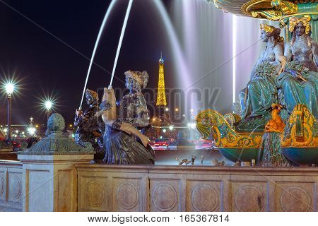 Northern Fountain of River Commerce and Navigation at the Place de la Concorde at night, Eiffel tower in the background, Paris, France