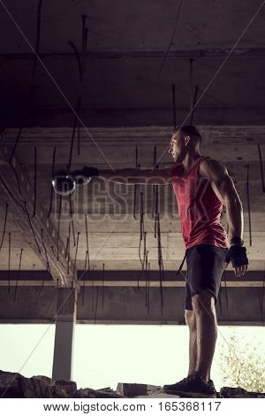 Side view of a young muscular athlete working out lifting a kettlebell weight in an abandoned ruined building