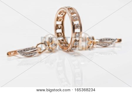 Elegant Gold Earrings With Pearls And A Chunky Ring With Small Diamonds