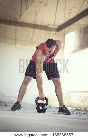 Front view of a young muscular athlete working out lifting a kettlebell weight in an abandoned ruined building