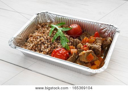 Healthy food in foil box on white wood. Russian kasha buckwheat porridge with dried tomatoes and beef stew. Restaurant dishes delivery, lunch for diet