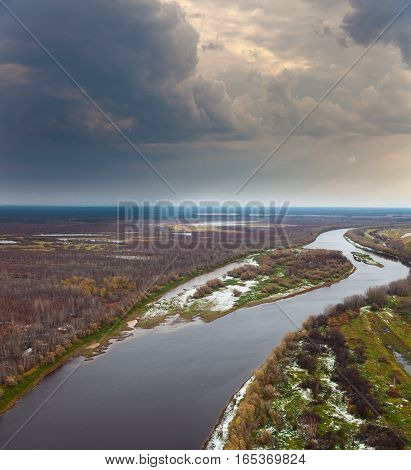 Top view of forest river with first snow in late autumn.