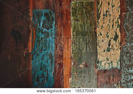 Texture of table or floor with old brown planks roughly painted with subdued blue, green and beige