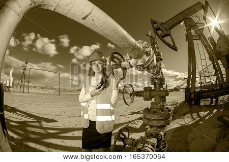Woman engineer in the oil field talking on the radio wearing helmet and work clothes. Industrial site background. Oil and gas concept. Toned sepia.