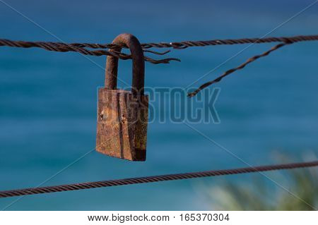 Closed padlock on cut iron rope represents insecurity