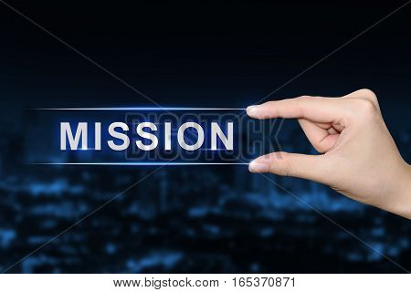 hand pushing mission button on blurred blue background
