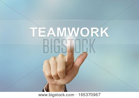 business hand pushing teamwork button on blurred background