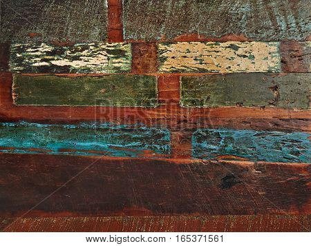 Rich texture of table or floor with old worn brown planks roughly painted with subdued blue, green and beige