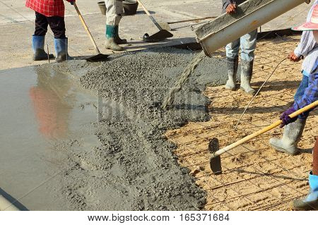 Worker pouring cement for building the floor