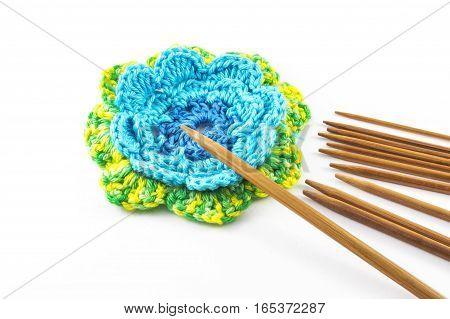 Crochet hooks and flower on white background