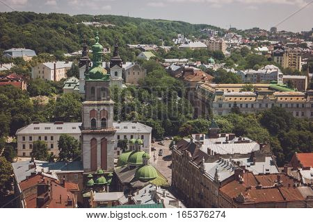 Town and green trees. Tower of church with cross. Beauty of the God's temple.