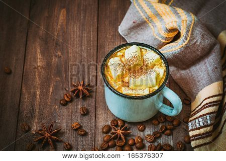Cup of coffee with marshmallow on rustic wooden background. Selective focus.