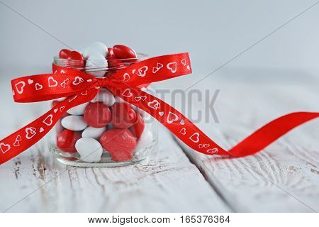 Colorful candy jar decorated with a red bow with hearts on white wooden background. Valentines day concept.