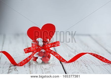 Colorful candy jar decorated with a red bow and red paper heart on white wooden background. Valentines day concept.
