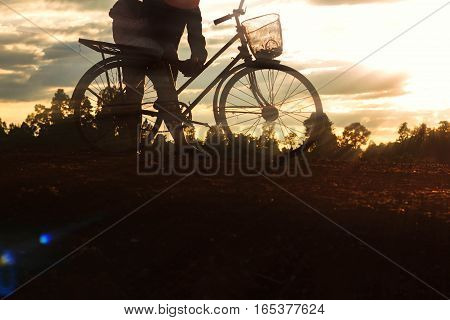 Farmer and child on a bicycle at the sunset.
