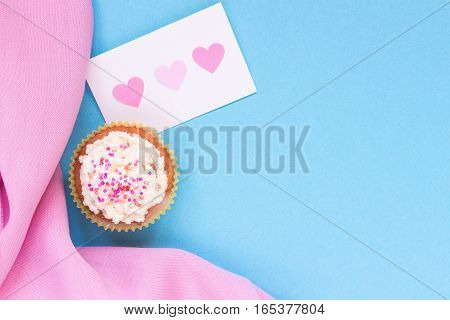 Valentine's Day background. Valentine's day card and cupcake with copy space on the blue background.
