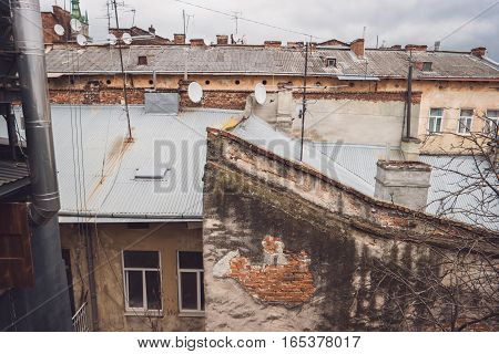 Rooftops of town buildings. White satellite dishes. Old architecture and new technologies.