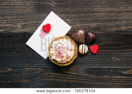 Valentine's Day background. Valentine's day card, chocolate and cupcake on the wooden dark background.