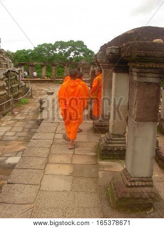 SIEM REAP, CAMBODIA - AUGUST 06, 2014 - Unidentified young buddhist monks walking inside the ruins of Baphuon temple