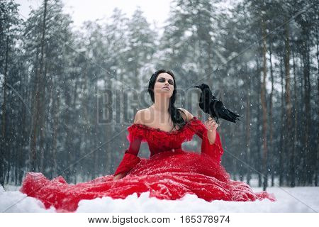 Woman witch in red dress with raven in her hand sits on snow in forest. Her long dress lying on snow and she closed her eyes. Around snowing and snowflakes fall on hem of her dress.