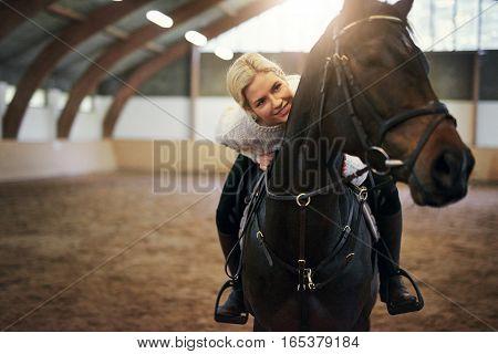 Smiling Blonde Female Leaning On Black Horseback