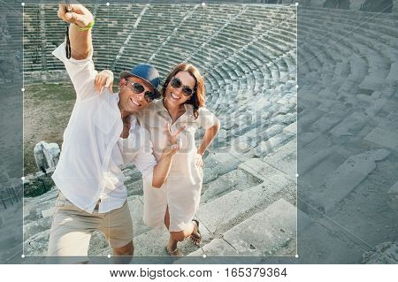 Funny couple take a selfie photo in antique amphitheatre in Side Turkey