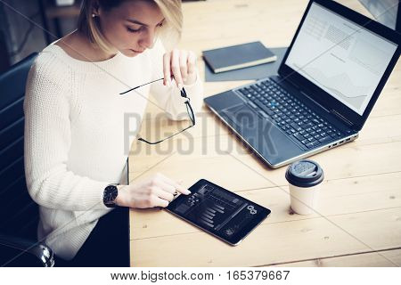 Top view of young beautiful woman working at the wooden table with mobile devices.Female hand touching digital tablet.Graph and diagram on laptop display.Horizontal, blurred background