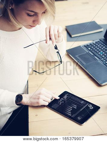Top view of young beautiful woman working at the wooden table with mobile devices.Female hand touching digital tablet.Graph and diagram on laptop display.Vertical, blurred background