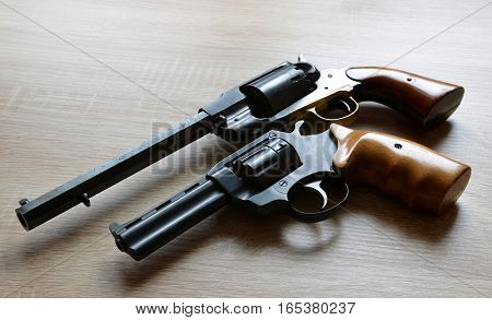 Two revolver pistols on a wooden board.