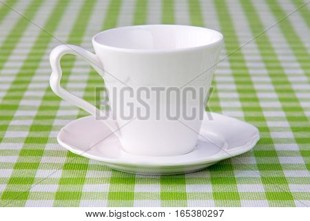 Empty cup on the checkered tablecloth texture