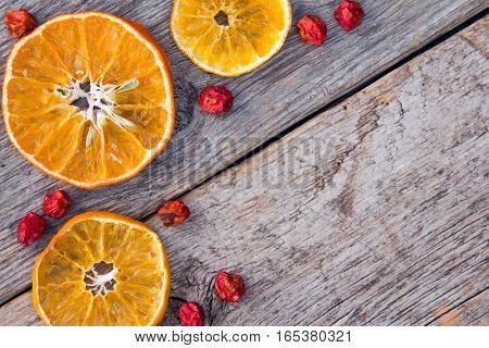 Dried oranges with ashberry on the old wooden background.