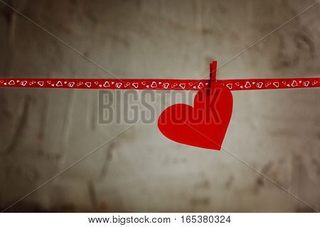 Red Paper heart hanging on red ribbon on grey background. Concept Valentines day