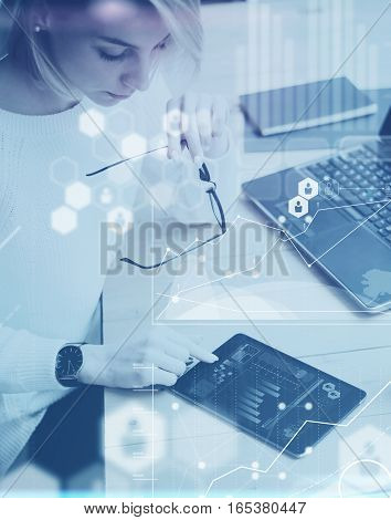 Concept of digital screen, virtual connection icon, diagram, graph interfaces.Top view young beautiful woman working at the wooden table with mobile devices.Vertical, blurred background