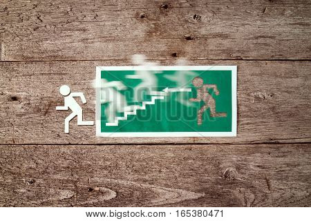 Exit sign on old wooden wall with man figure running to doorway