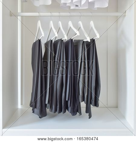 Row Of Black Pants Hanging In White Wooden Wardrobe