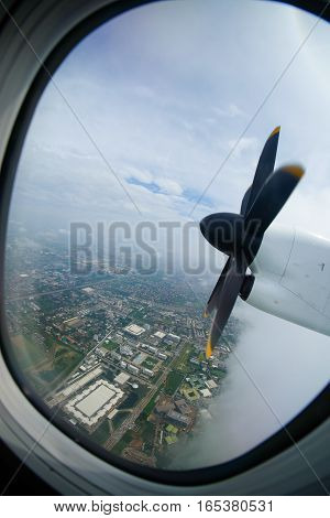 Plane propeller seen through the window on the city