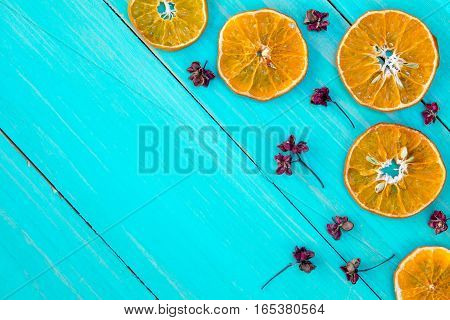 Orange slices and dry herbs on the blue wooden background.