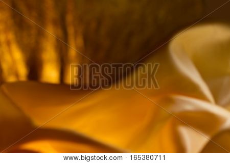 Wonderful game of light and shadow on dark golden cloth background with curves shapes and texture